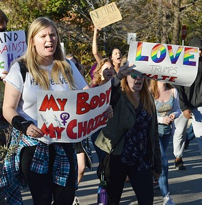 """Young woman carries """"My Body, My Choice"""" sign in march against Donald Trump."""
