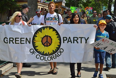 Green Party of Colorado members carry a large banner in campaign march.