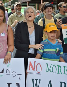Jill Stein, Green Party candidate for President,  with hands on shoulders of young boy next to her, marches along side of supporters at campaign event in Colorado.