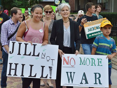 "Jill Stein, Green Party candidate for President, marches along side of supporters at campaign event in Colorado, including young woman carrying ""Jill Not Hill"" sign and young boy with ""No More War"" sign."