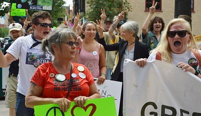 Jill Stein, Green Party candidate for President, marches along side of supporters at campaign event in Colorado. Stein and other raise hands in peace sign.