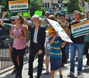 Jill Stein, Green Party candidate for President, marches along side of supporters carrying sign and chanting, at campaign event in Colorado.