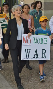 "Jill Stein, Green Party candidate for President, carries ""No More War"" sign with young boy as they  march together at campaign event in Colorado."