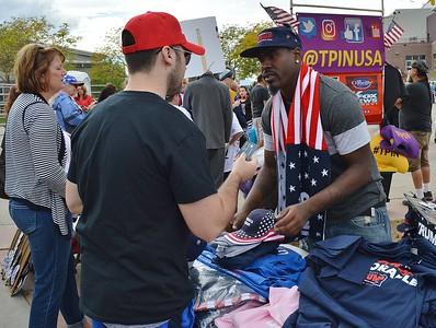 Vendor at Donald Trump rally, standing ion front a of a table of merchandise, sells campaign items to a Trump supporter. Vendor is wearing a Trump hat and American flag/Trump scarf.