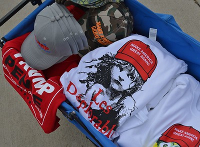 "Table of Donald Trump campaign merchandise including shirt with drawing of ""Les Miserable"" character wearing Trump hat. Slogan on shirt says ""Les Deplorables""."