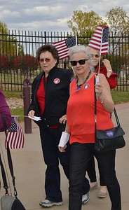 Two women carrying American flags in line for a Donald trump rally.
