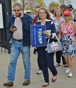 Woman holding Trump For President sign in line at a Trump rally.