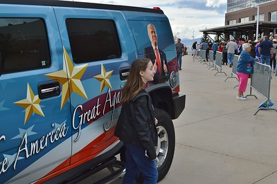 Young girl posing for a picture in front of a van with large picture of Donald Trump on the side.