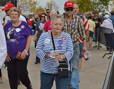 Senior woman wearing Donald Trump stickers, in line for a Donald Trump rally, other Trump suppoters in line behind her.