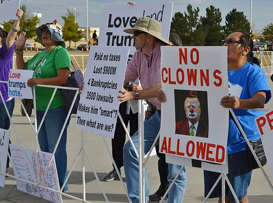 Anti Donald Trump protesters with signs including one with picture of Trump in clown make-up.