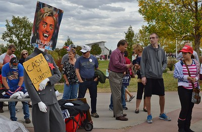 Donald Trump supporters in line for a rally, turn to look at an anti Hillary Clinton poster portraying her as the devil.