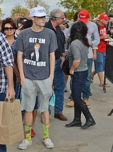 "Young man wearing a ""Get'em Outta Here"" shirt depicting Donald Trump, stands in line for a Trump rally."