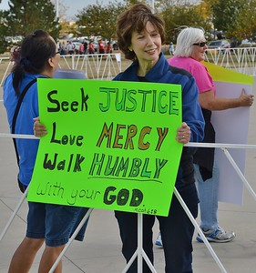 Anti Donald Trump protester holding sign with quote from the Bible on it, outside a Trump rally.