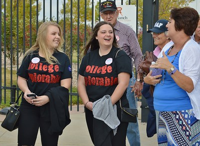 "Two young women wearing ""College Deplorable"" shirts, talking to other Donald Trump supporters in line for a rally."