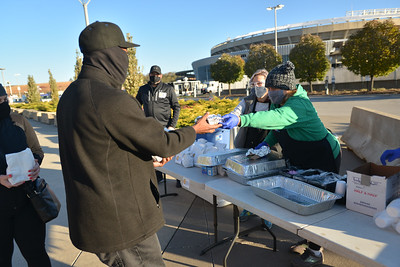 Jacki (cq) Becker hads out a breakfast sandwich to Pierre Culbert who brought his friend to vote at Arrowhead Stadium on Tuesday morning. Becker and other voluteers were on hand at the Kansas City Chiefs' facility to hand out food as part of the World Central Kitchen's effort to assist voters across the country.