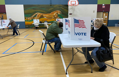 Voters at Chapel Lakes Elementary School in Lee's Summit mark their ballot early Tuesday morning inside the school's gym.