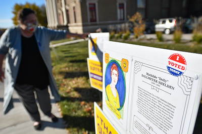 """Virginia Wallace , the current president of KC Athenaeum Club, reads from one of the placards posted near the building on Tuesday in Kansas City. The pages display drawings and information about suffragists from Kansas City's past. Voters were been encouraged to visit the location and post their """"I voted"""" stickers on the signs."""