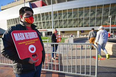 Chris Sathos, the Kansas City Chiefs manager of partnership development, stands with other stafff members pointing out the safety protocols as voters enter the polling location at Arrowhead Stadium on Tuesday morning.