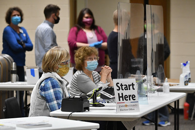 Poll workers wait for voters at Indian Creek Technology Center in Overland Park on Tuesday. Officials there reported a light but steady crowd early in the day.