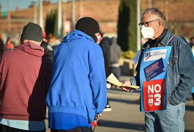 Everett Murphy, a volunteer with the League of Women Voters, informs voters about Amendment 3 at Arrowhead Stadium on Tuesday morning.