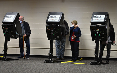 An election worker at Indian Creek Technology Center in Overland Park gives instruction to a voter while others make their selections in Tuesday's election. Officials there reported a light but steady stream of voters throughout the day.