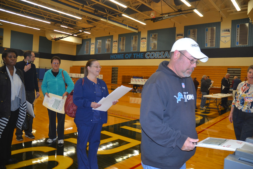 . Voters � including Doug Dufrin and Mary Ann Bryan � turning in their ballots with the help of election worker Catherine Roller at Waterford Mott High School on Nov. 8, 2016. Anne Runkle / Digital First Media.