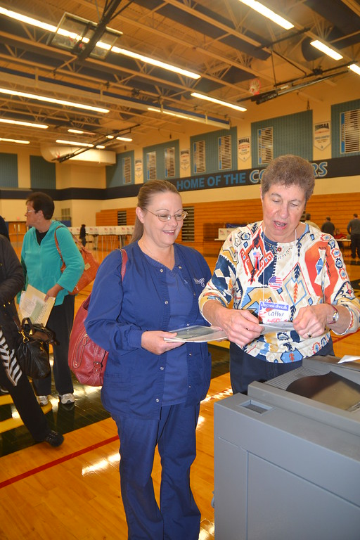 . Mary Ann Bryan finishes her voting with the help of election worker Catherine Roller at Waterford Mott High School on Nov. 8, 2016. Anne Runkle / Digital First Media.