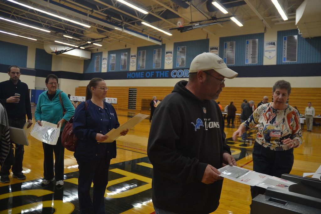 . Voters turning in their ballots with the help of election worker Catherine Roller at Waterford Mott High School on Nov. 8, 2016. Anne Runkle / Digital First Media.