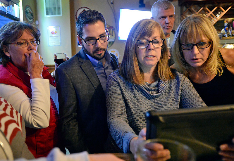 Trish Will , left, Blas Estrada, center left, supporters of the Thompson tax issues, and Thompson education board members Pam Howard, center right, and Denise Montagu, react as results come in showing that ballot issues 3D and 3E were failing during a watch party Tuesday, Nov. 8, 2016, at the Pourhouse in downtown Loveland. (Photo by Jenny Sparks/Loveland Reporter-Herald)