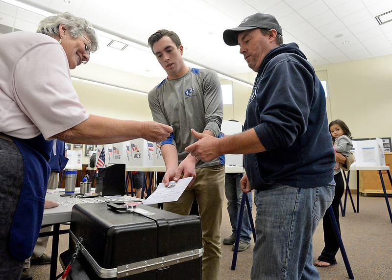"Election judge Syvia Fiscus, left, hands Dusty Allen his ""I Voted"" sticker as Parker Allen, center, drops his ballot into the box after voting in his first presidential election Tuesday, Nov. 8, 2016, at the Police and Courts Building in downtown Loveland. (Photo by Jenny Spaks/Loveland Reporter-Herald)"
