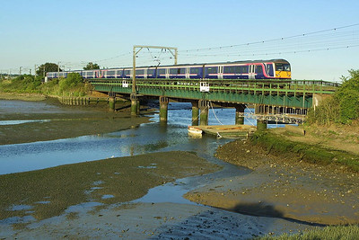 A pair of Class 360 units lead by 360107 cross Manningtree Viaduct on 06/07/2004 whilst working 1Y63 1928 Ipswich-London Liverpool Street.