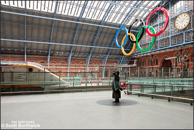 At the blocks under the 2012 London Olympic Rings, 3108 stands at London St Pancras International after arriving with 9129 1220 Brussels Midi-London St Pancras International on 16/10/2011. Paul Day's 9m tall bronze statue 'The Meeting Place' is also visible underneath the famous St. Pancras Clock (re-constructed by the original makers Dent). The 8.5ft sculpture of Sir John Betjeman by Martin Jennings looks admiringly at the Eurostar train.