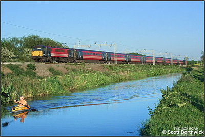 87008 'City of Liverpool' speeds northwards alongside the Oxford Canal at Ansty, overtaking a gentleman out for an evening paddle, whilst working 1S94 1830 London Euston-Glasgow Central  on 18/05/2004.