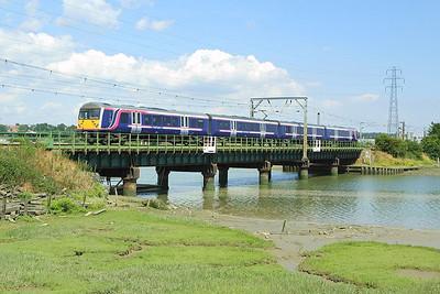 360113 works 1Y39 1330 Ipswich-London Liverpool Street across Manningtree Viaduct on 06/07/2004.