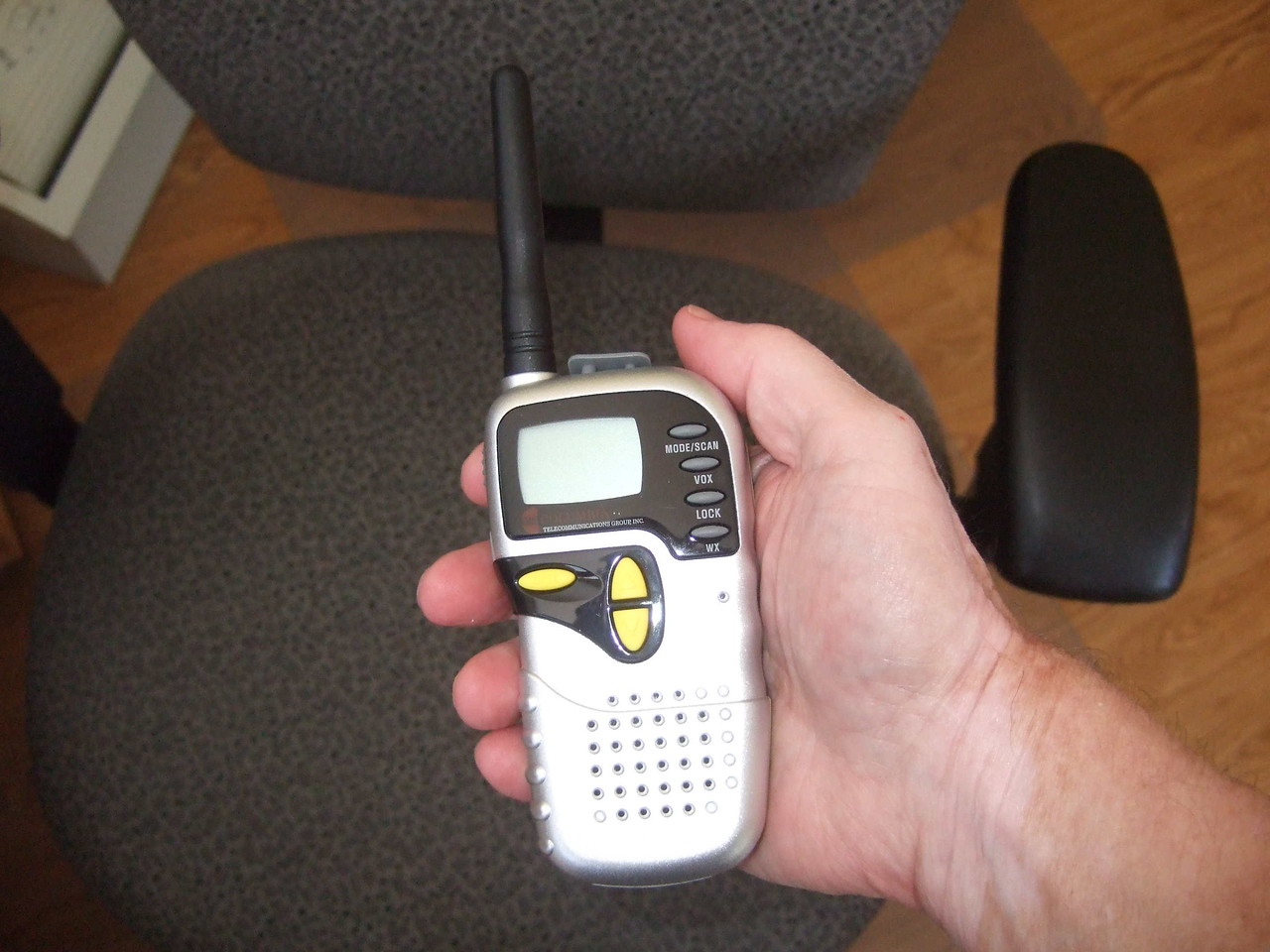 The radio is comfortably large, fitting the hand nicely. The gray part sticking up at the top is the cover for the mic-earpiece jacks. Note that the base is rounded - it won't stand up on the base, which is aggravating.<br /> <br /> The horizontal button near my finger is the CALL button - it transmits a deedle-deedle to all radios on the frequency. The two vertical yellow buttons are the UP and DOWN button; when it receive, they control volume. The gray button on top near my thumb is the MODE button - pressing it cycles through the various modes, then you use the UP or DOWN button to make selections within a MODE (select channels, for example, or CTCSS tones). The second gray button toggles VOX, the third gray button locks/unlocks the radio, and the bottom gray button toggles WX from NOAA.