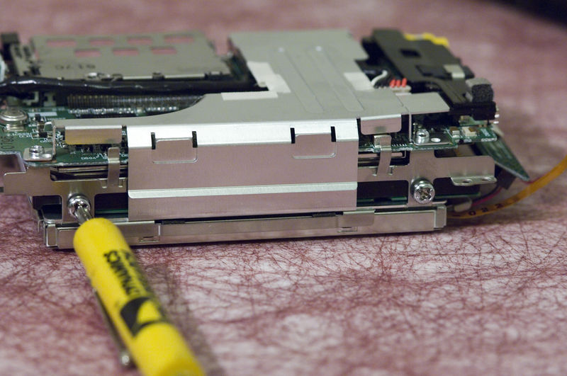 These three photos show removal of the four hard drive mounting screws.