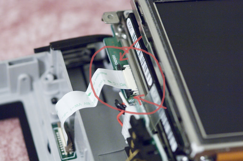 By carefully pulling the black edges (pointed to by arrows) away from the connector you will be able to release the cable.