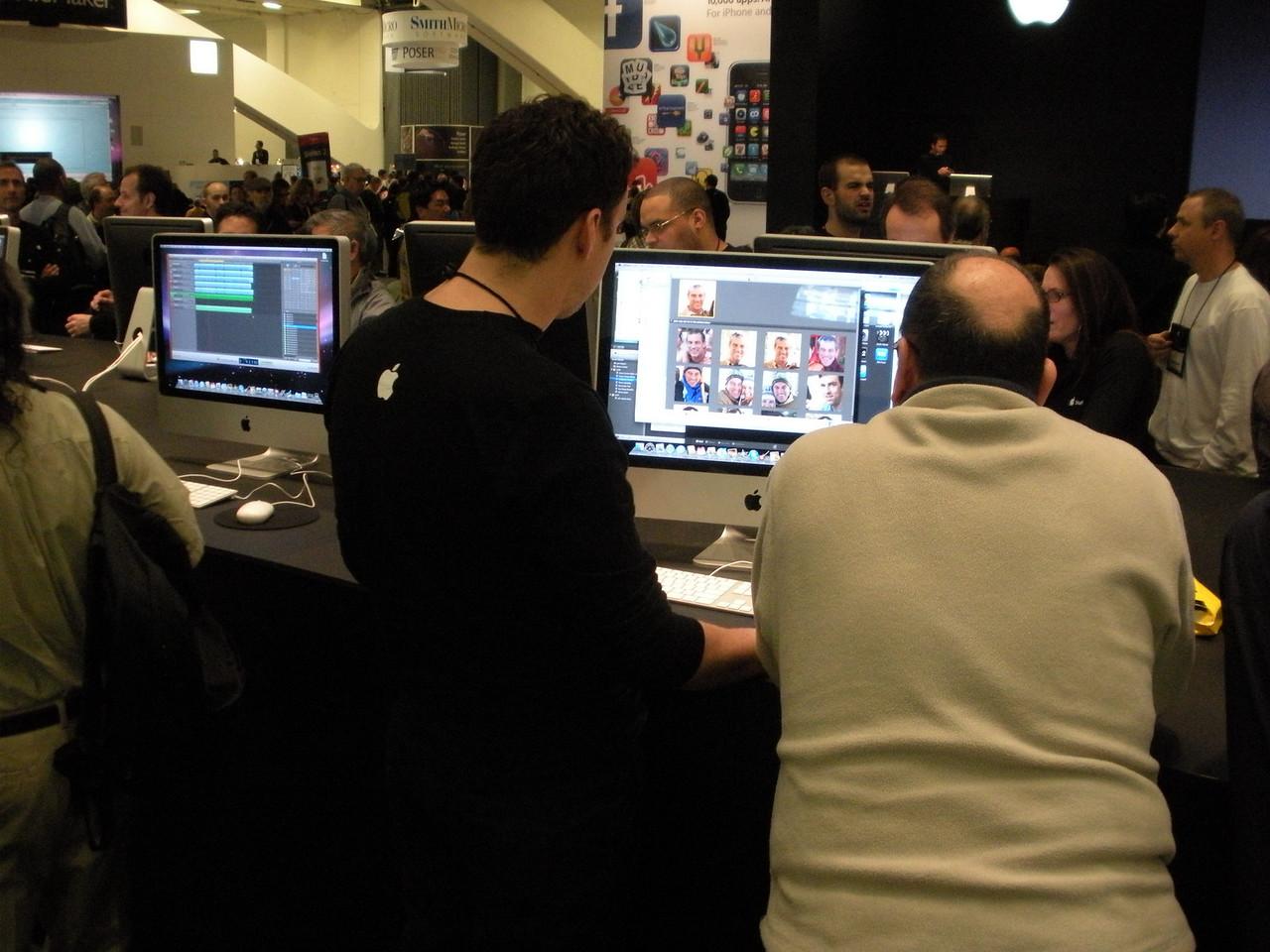 Apple-eers demonstrating software on iMacs.