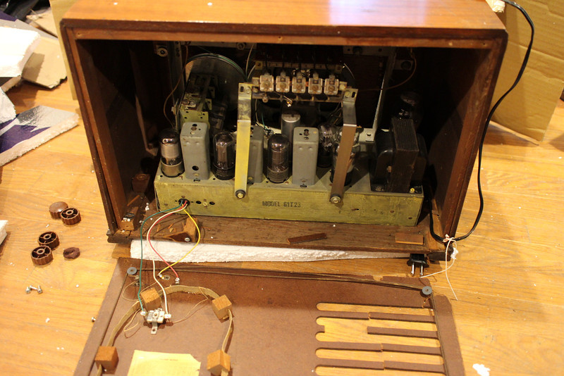 Lower right rear panel mounting block broken free and near left side of cabinet.  Corner piece of rear panel still attached to it.  Loose front panel mounting block visible on left side of cabinet along side of chassis.