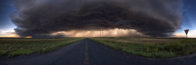 """""""Panhandle Magic""""  Texas Panhandle  My family and I were returning from vacation in Colorado when we came upon this amazing storm.  It stretched from horizon to horizon, and the light filtering through from the back side created some of the most amazing colors I have ever seen.  I knew we had to stop and shoot it, and I was luckily able to find this deserted highway right off the main road.  Technical Details: Shot with Canon 30D and Canon 10-22mm lens at F10 and 1/8.    Panorama created from 30  vertical bracketted shots."""