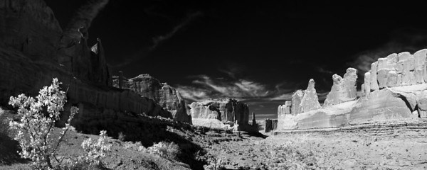 """Park Avenue in Shadow""  Arches National Park, UT  This is another shot from my vacation to Colorado and Utah in the Fall of 2008.  Arches National Park, near the town of Moab, UT is an incredible location filled with some of the most bizarre and interesting scenery you will find anywhere.  This particulation location is called Park Avenue.  This is an infrared image, which I chose due to the harsh lighting of mid day and with a desire to capture the interplay between the shadows and the light.  Technical Details: Shot with IR Modified Canon 10D and Canon 20mm lens at F16 and 1/40.    Panorama created from 10 vertical bracketted shots."