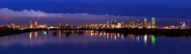 """""""Dallas Blue Hour""""  Dallas, TX Once or twice a year the Dallas are recieves enough rain to fill the levee of the Trinity River.  When this happens I like to get out and shoot the Dallas skyline.  A friend showed me this location and it really pulls all of the skyline together.  Technical Details: Shot with Canon 5d MK2 and Canon 10-22mm lens.    Panorama created from 5 bracketted horizontal shots."""