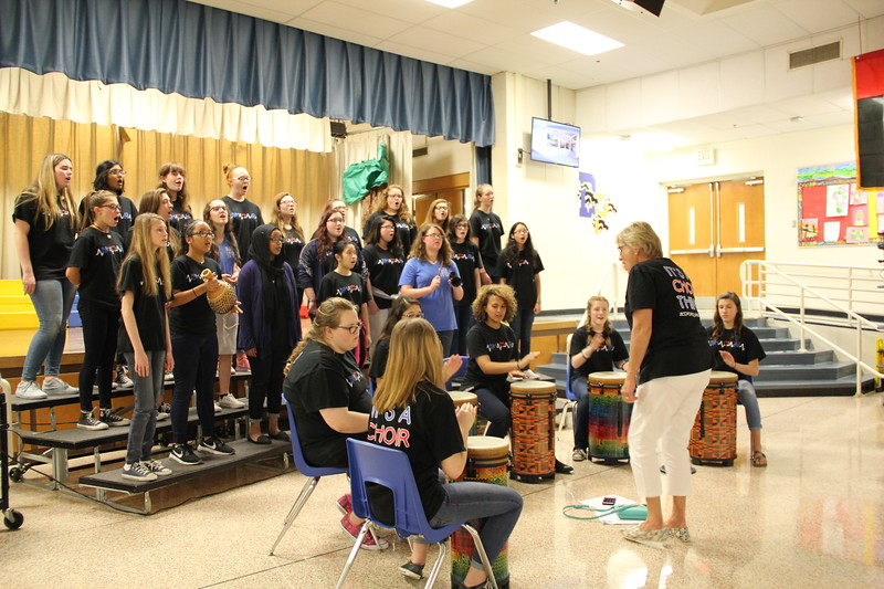 Students and staff perform song with various drums.