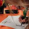 Guests practice writing with a feather quill.