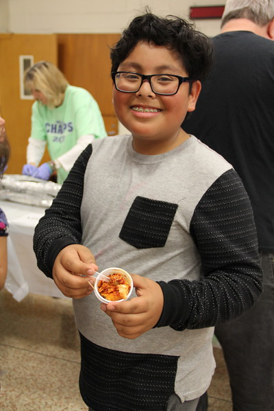 Student shows off food he's trying.