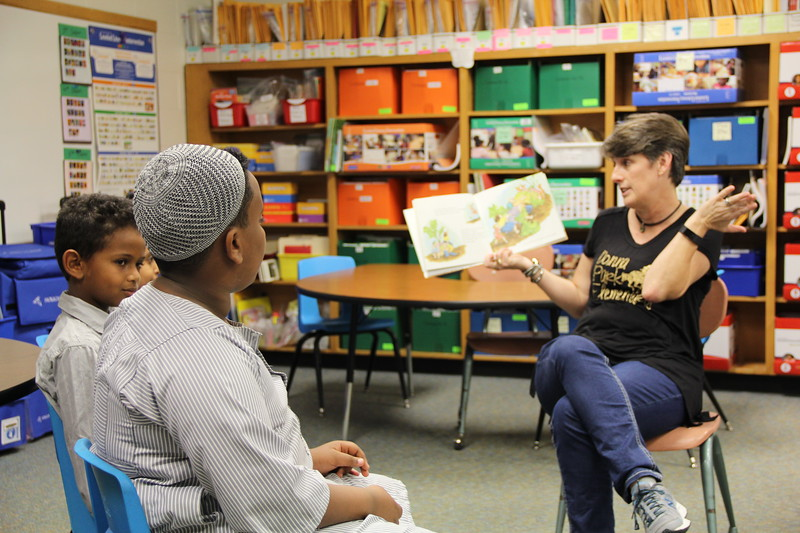 Guests listen to a story read by teacher.