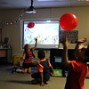 Students play with red balloons.