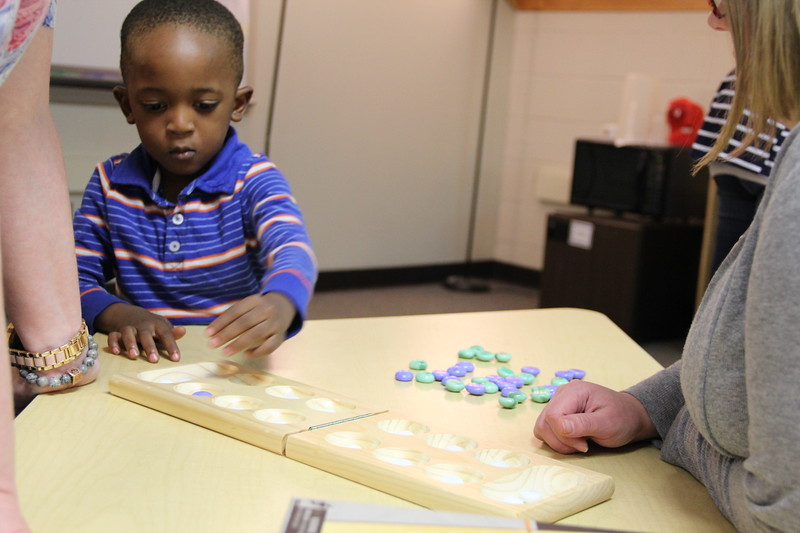 Children play a game of mancala.