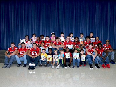 GCM Football Players read to the BP Hopper Grasshoppers
