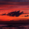 Dark dramatic clouds backlit by beautiful red sunset sky